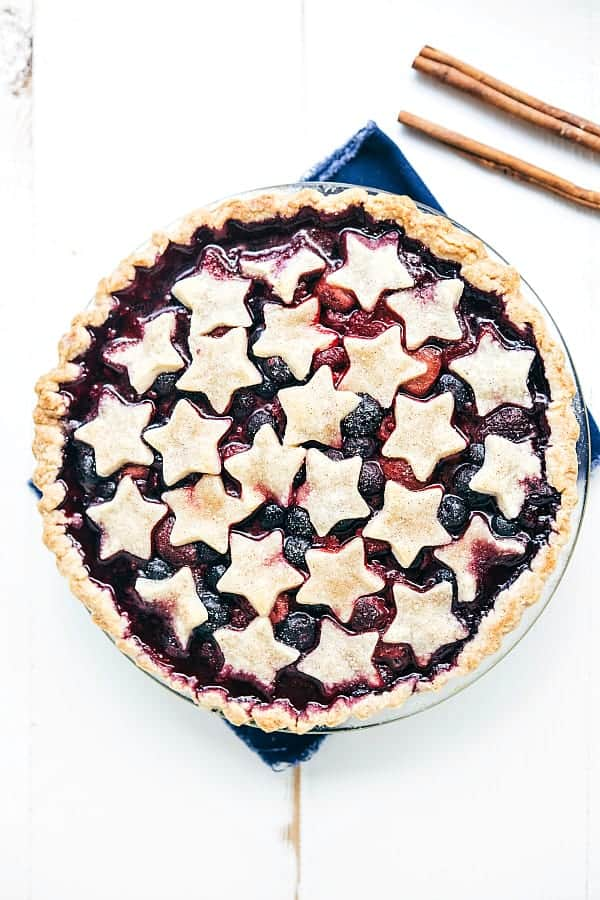 Tripple Berry Pice in a pie dish with star shaped pie top and two sticks of cinnamon on the side.