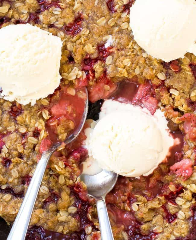 Strawberry Crisp with three scoops of ice cream on top with two metal spoons.