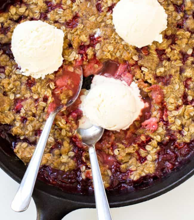 Strawberry Crisp in a large black skillet with three scoops of ice cream and two metal spoons.
