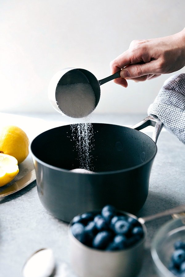 A cup of sugar being added to a pot.