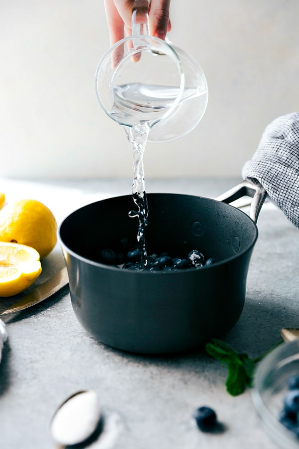 Water being added to a pot with fresh lemons on the side.