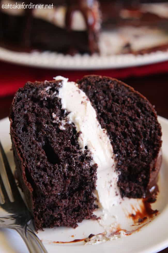 An up close photo fo Chocolate Whoopie Pie Cake on a white plate with a metal fork.