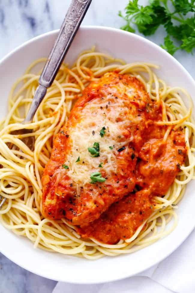 Creamy Tomato Italian Parmesan Chicken over noodles in a white bowl and a metal fork.