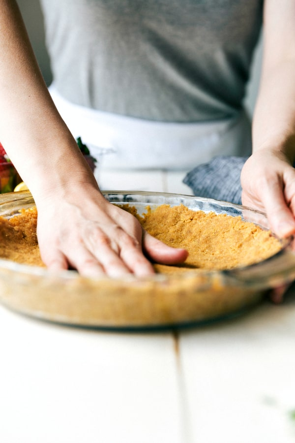 A hand pressing down the pie crust in the clear pie pan.