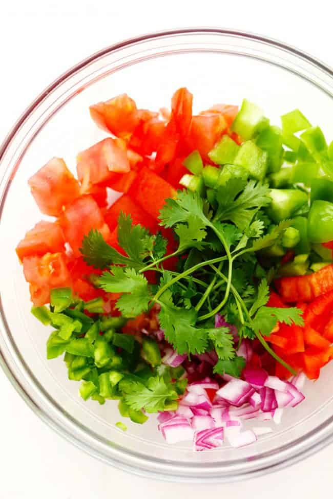 Ingredients for Slow Cooker Restaurant Style Garden Salsa in a clear bowl.