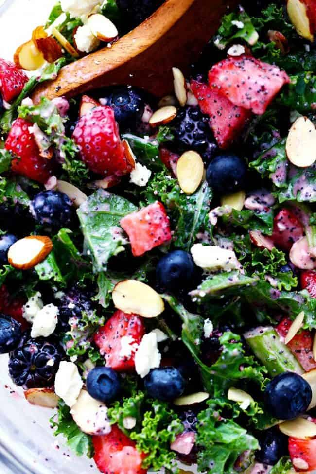Close up photo of Triple Berry Kale Salad with Creamy Strawberry Poppyseed Dressing in a clear bowl with a wooden spoon.
