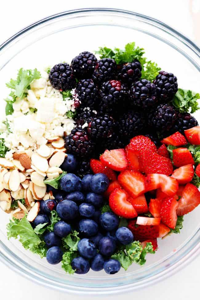 Triple Berry Kale Salad ingredients in a large clear bowl.