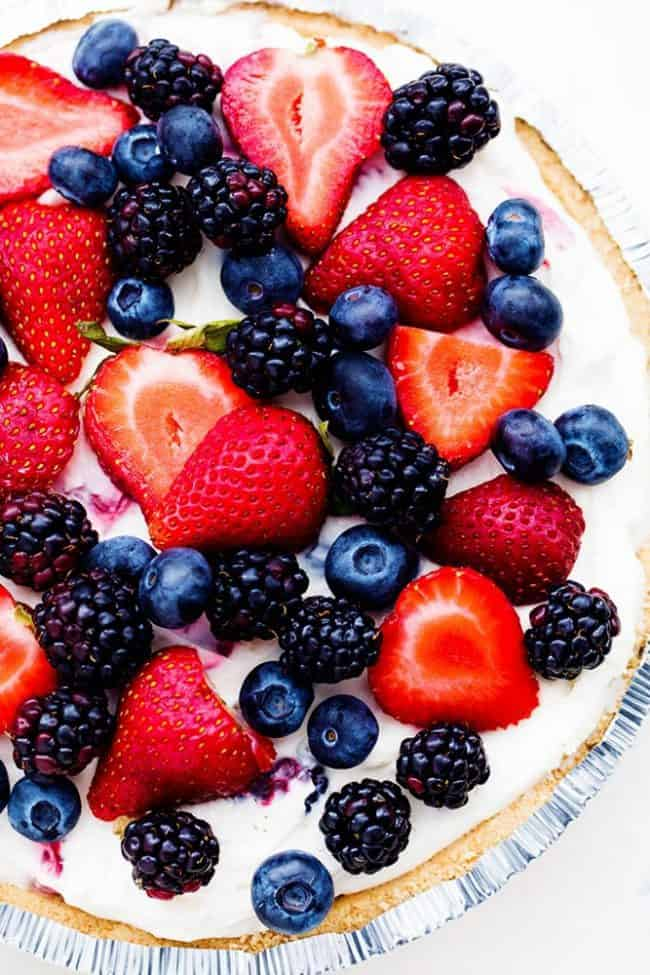 No Bake Very Berry Cheesecake in a pie tin with fresh berries on top.