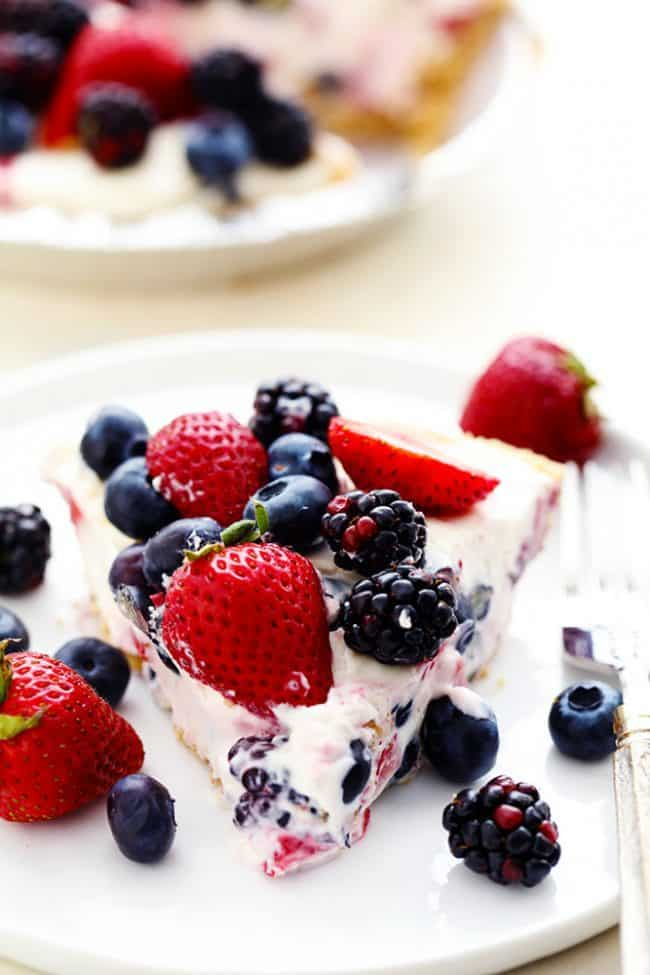 A slice of No Bake Very Berry Cheesecake on a white plate with fresh berries on top and on the side.