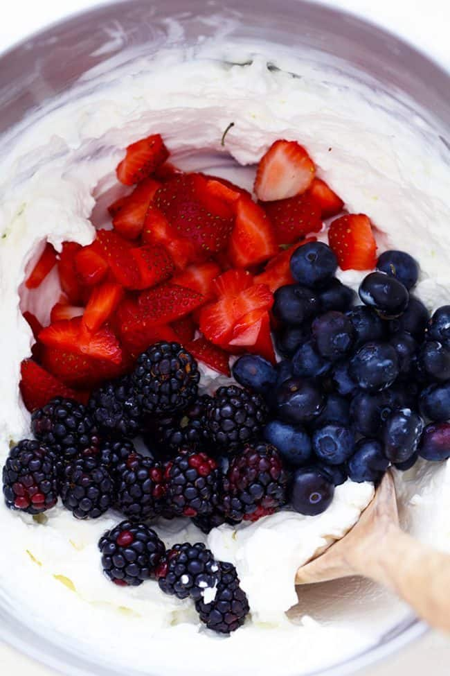 Strawberries, blackberries, and blueberries being mixed into the cheesecake mixture in a large mixing bowl.