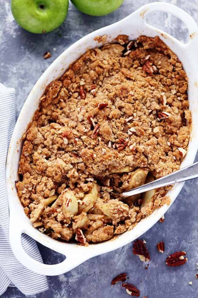 Apple Pecan Crisp in a white dish with a metal spoon.