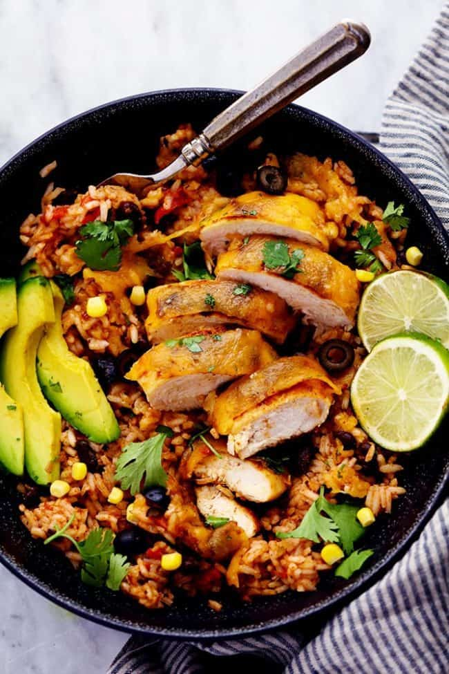 Cheesy Fiesta Chicken and Rice Skillet in a black bowl with slice avocado and limes on top with a metal spoon.
