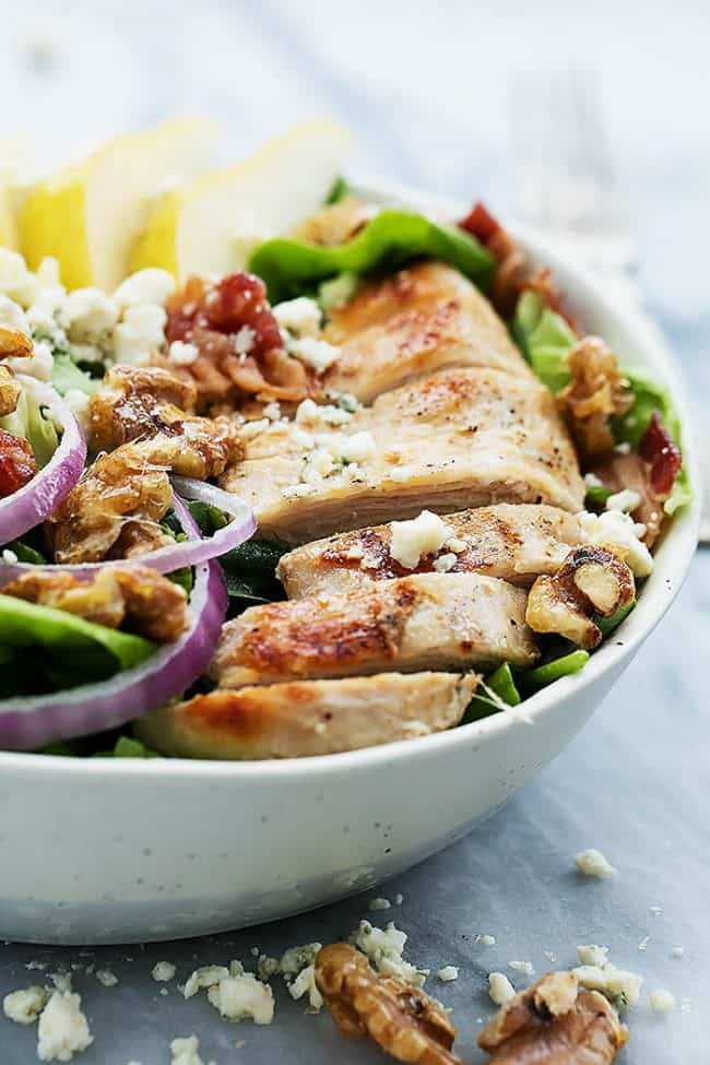 Grilled Chicken, Bacon, and Pear Salad with Poppyseed dressing in a white bowl.