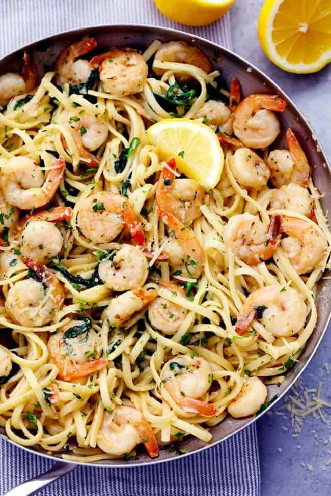 Lemon Garlic Parmesan Shrimp Pasta in a skillet with fresh lemons on the side.