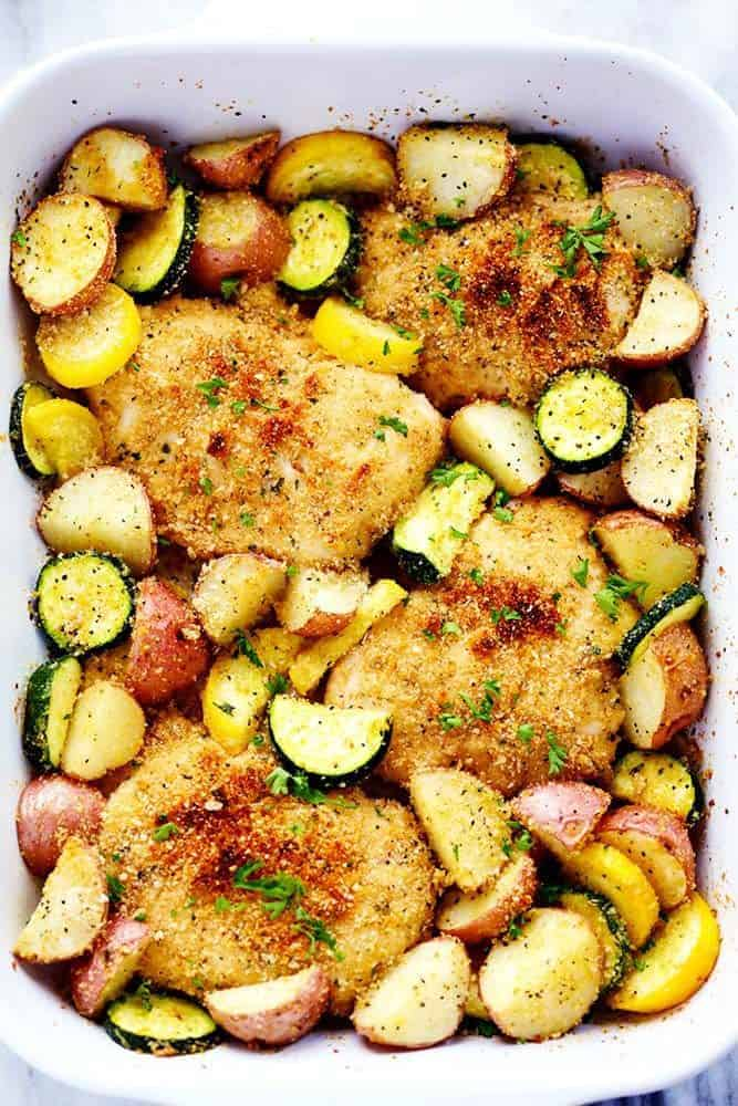 One Pan Crispy Parmesan Garlic Chicken with Vegetables in a white casserole dish.