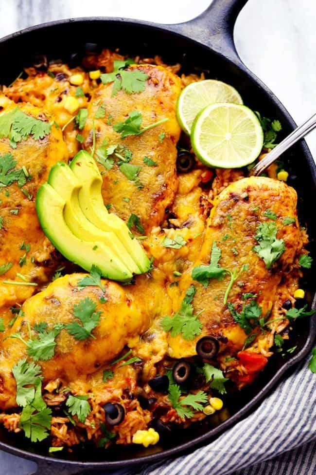 Cheesy Fiesta Chicken and Rice Skillet with freshly sliced avocado and limes on top.