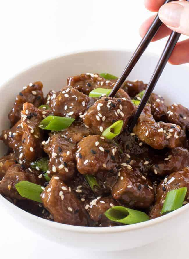 Beef teriyaki in a white bowl garnished with scallions and eating with black chopsticks.