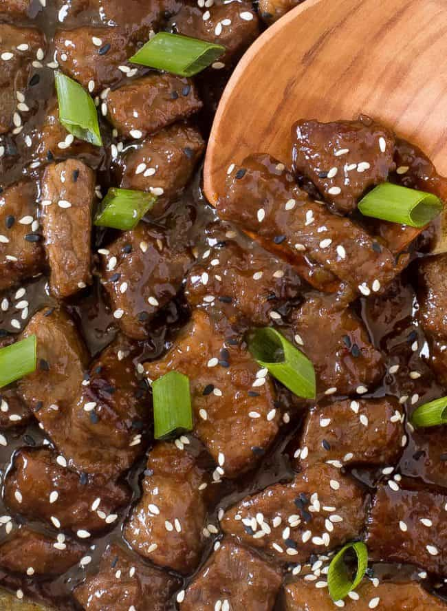 Up close photo of beef teriyaki garnished with sesame seeds and green scallions with a wooden spoon stirring it up.