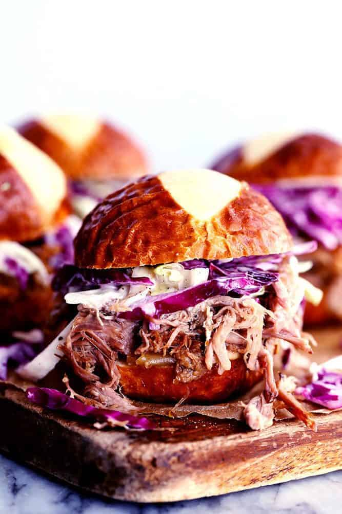 Sweet Carolina pulled pork sliders on a wooden cutting board.