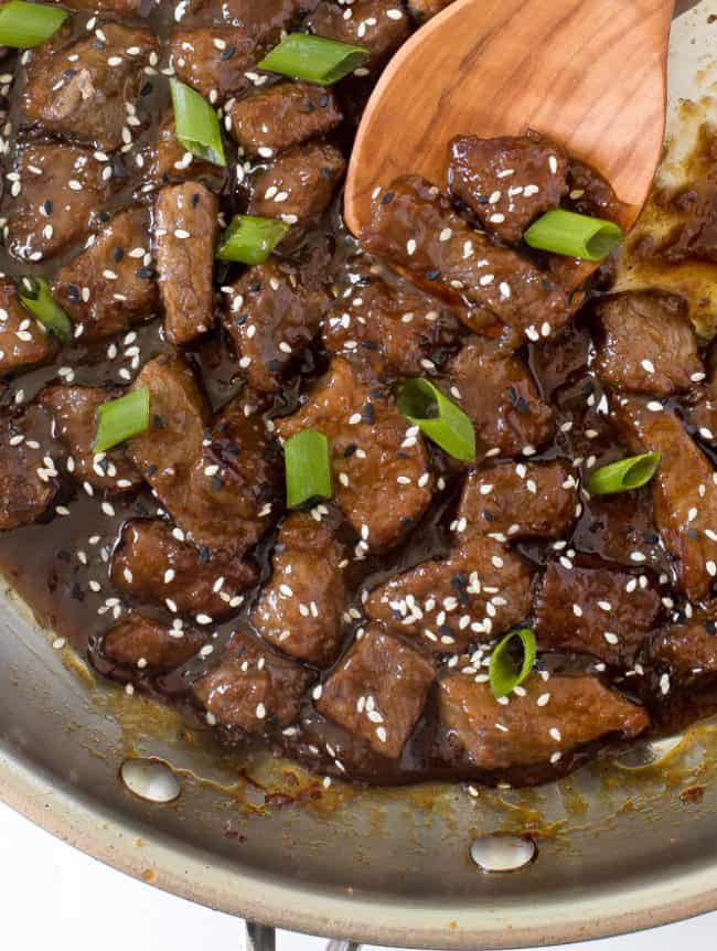 Teriyaki beef in a skillet with a wooden spoon.