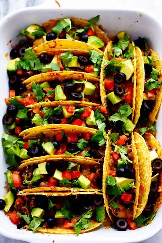 Beefy baked tacos lined up in hard shell tacos garnished with tomatoes, avocados and black olives in a white casserole dish.