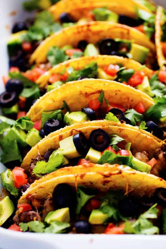 Hardshell tacos lined up in a row garnished with black olives, tomatoes and cilantro on top in a white casserole dish.