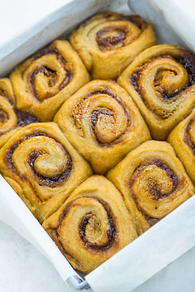 """Pumpkin cinnamon rolls in a 9 x 9"""" pan with parchment paper."""