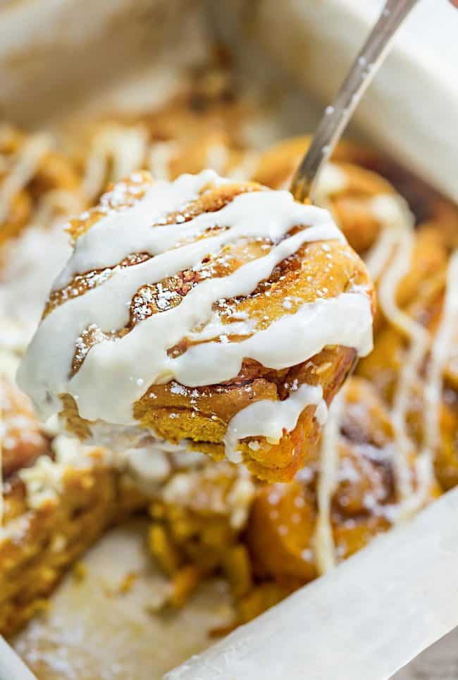 Pumpkin cinnamon rolls with frosting on top.