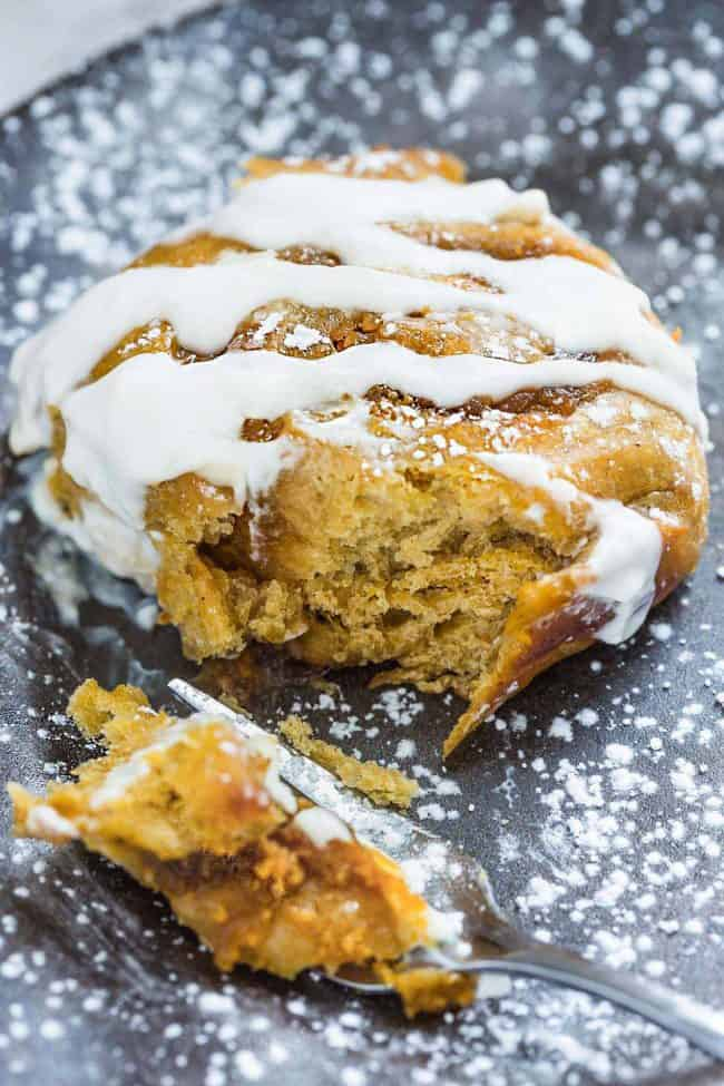 Pumpkin cinnamon rolls with frosting overtop and a fork taking a bite out of it.
