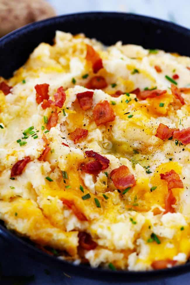 Mashed potatoes with bacon pieces as a garnish in a black bowl.