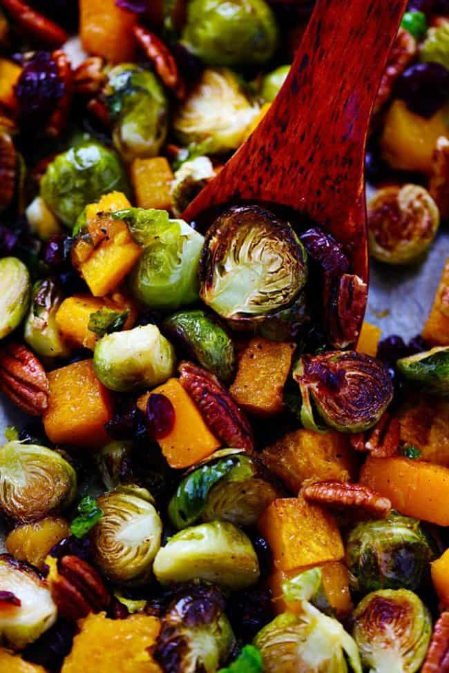 Maple Roasted Brussels Spouts and Butternut Squash with a wooden spoon scooping up the vegetables.