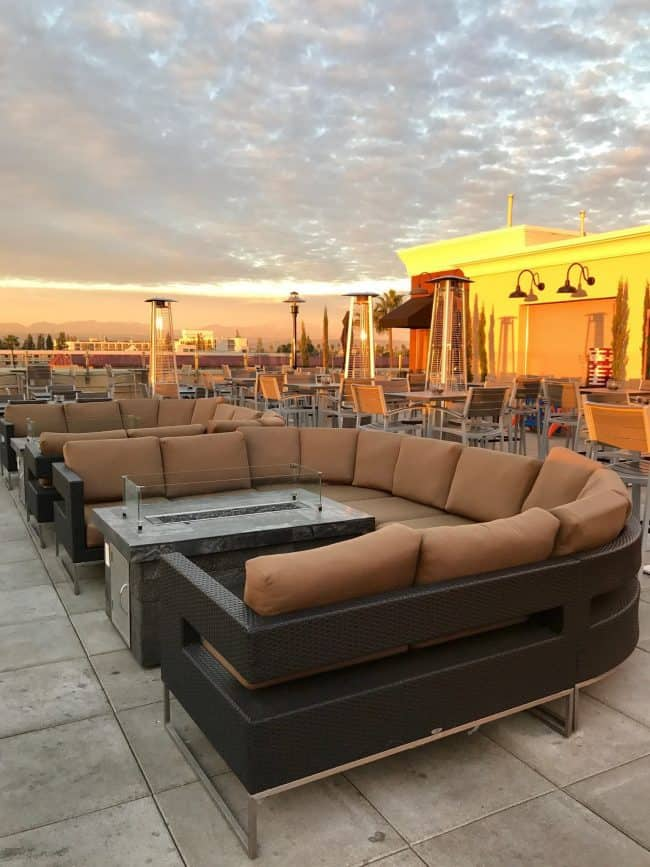 A photo with a couch on top of the roof top at the hotel with the sunrise.