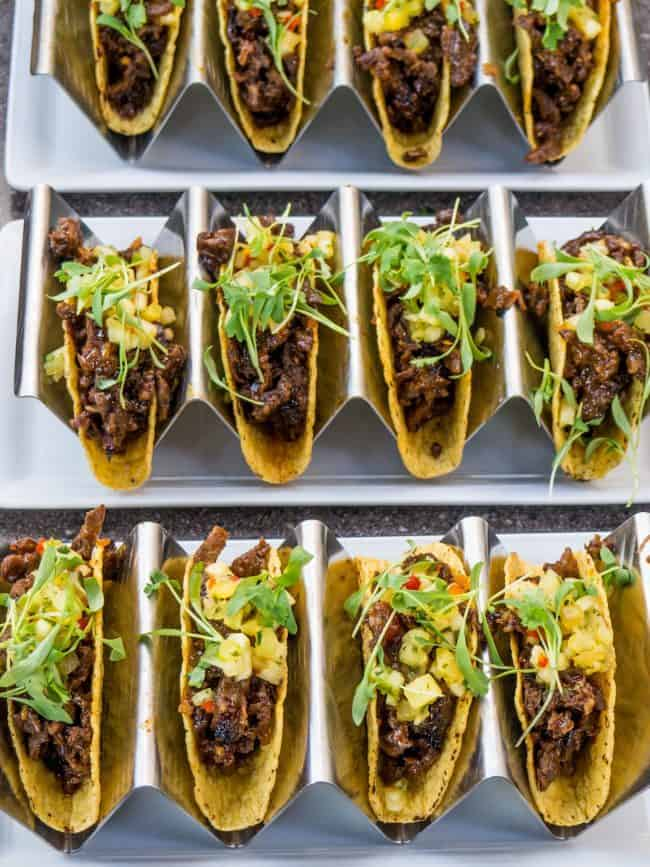 Rows of hardshell tacos with meat and lettuce on dividers.