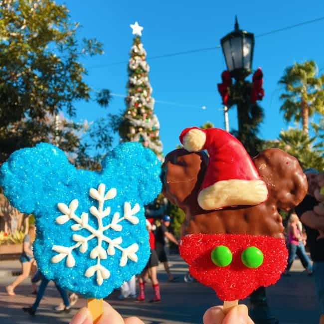 A photo with two Christmas Mickey Mouse ice cream bars. One is blue with a snowflake on itSpace and the other looks like a Santa Claus with a Santa hat, red frosting and two green buttons for the pants