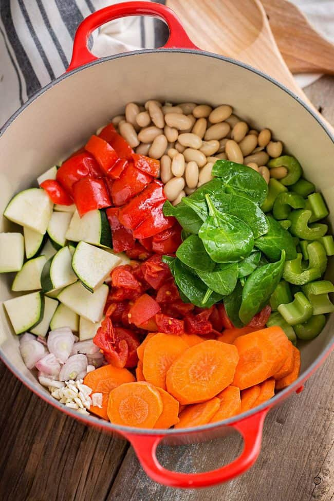 Sliced up carrots, red peppers, celery, zucchini, and Beans with onions and garlic all put into a large red pot.
