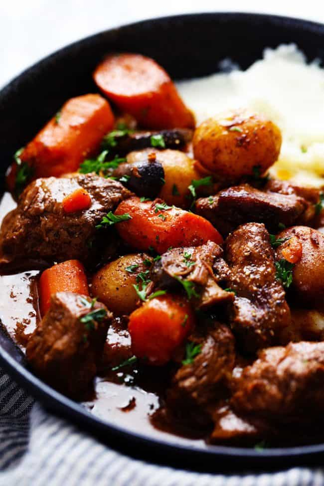 slow Cooker Beef Bourguignon with mashed potatoes on a plate up close photo