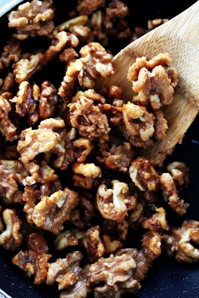 Candied walnuts being cooked in a black skillet while being stirred by a wooden spoon.