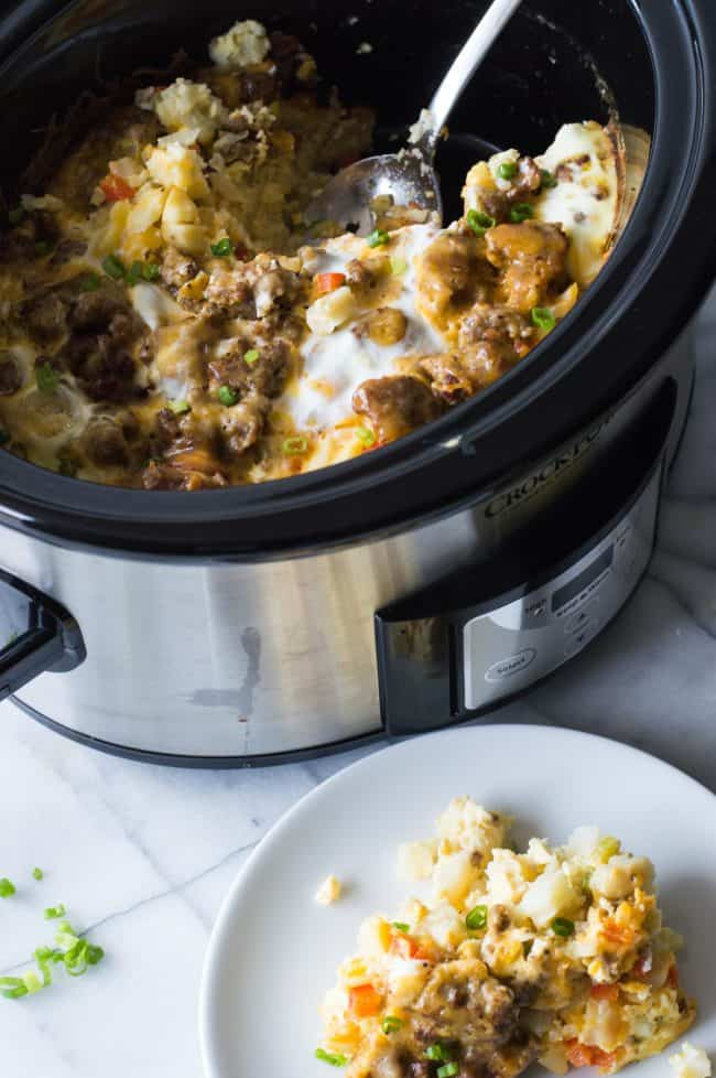 Breakfast casserole in a slow cooker dish with the spoon and then slow cooker. On the side of the slow cooker is the slow cooker breakfast casserole and a white plate ready to be served.