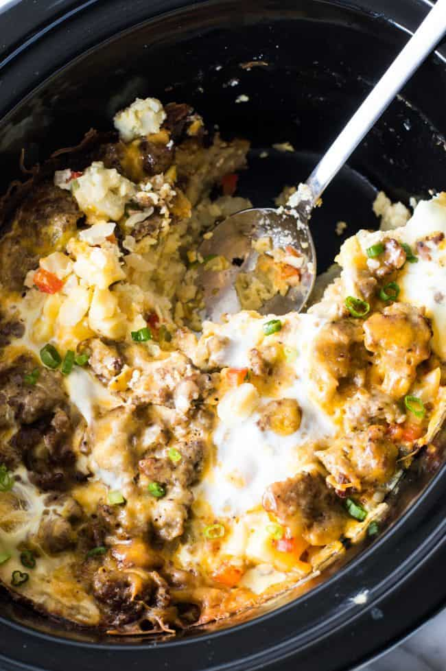 Breakfast casserole in the slow cooker with the spoon dishing out some of the casserole.