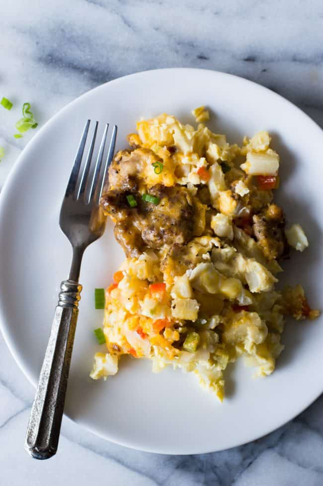 Slow cooker breakfast casserole on a white plate with the fork on the left side.