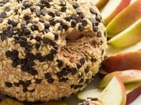 This Snickers Cheese Ball is perfect for holiday potlucks and gatherings! Loaded with caramel, chocolate and peanut butter, it's perfect served with apple slices, other fruit, and graham crackers.