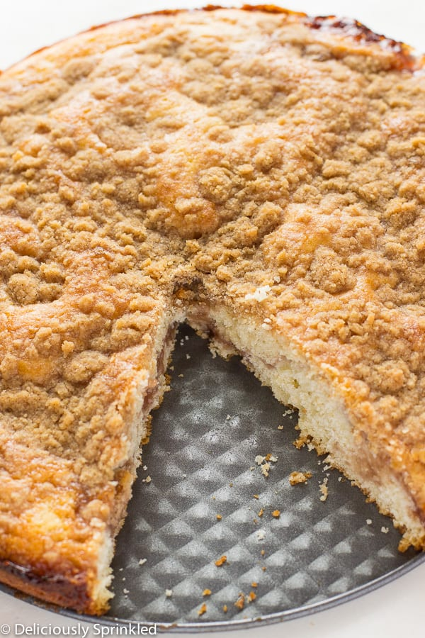 Strawberry jam crumb cake with a slice out of it.