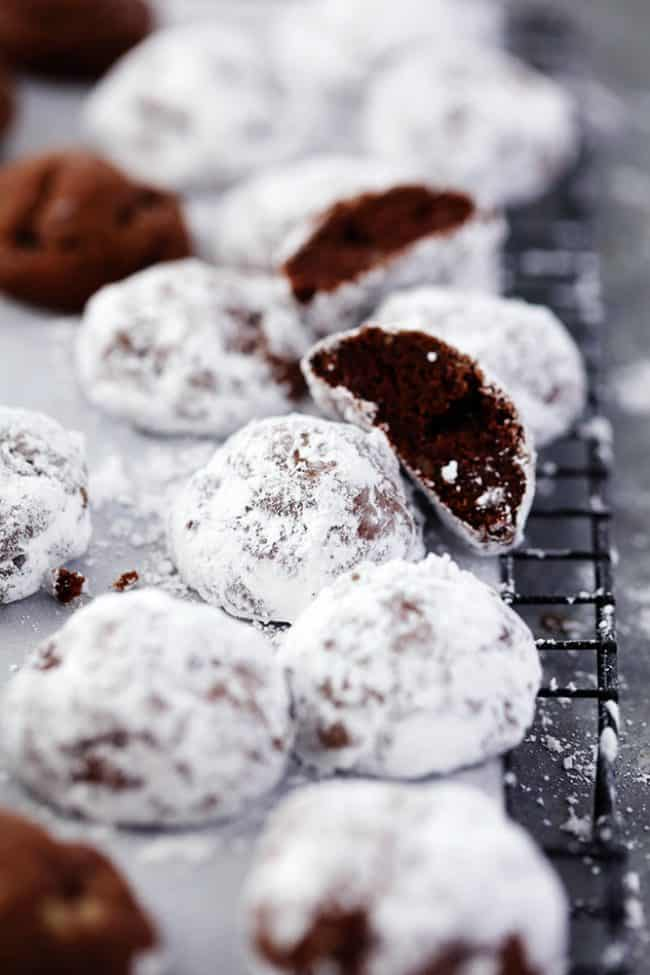 Chocolate Snowball cookies stacked on top of each other on parchment paper on a black cooling rack.