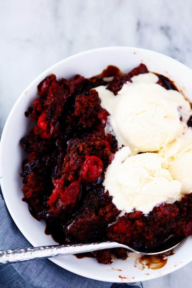 Slow cooker cherry chocolate hot fudge cake in a white bowl with a spoonOn the side with three vanilla ice cream scoops on top.