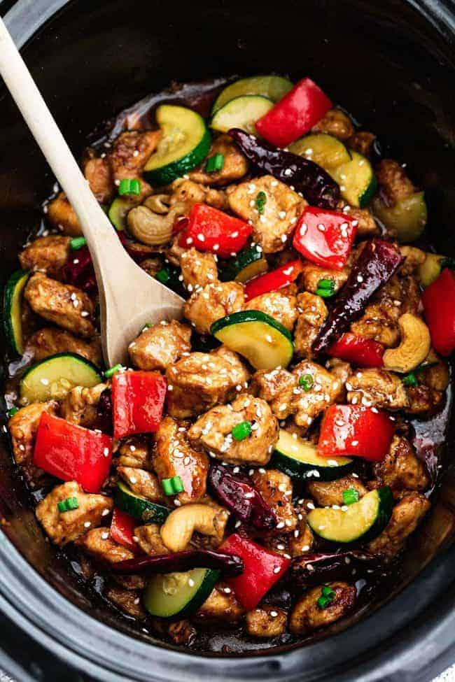 Skinny Slow Cooker Kung Pao Chicken in a slow cooker with a wooden spoon.