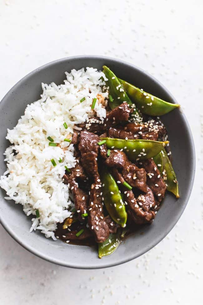Honey sesame beef on a black plate with white rice.