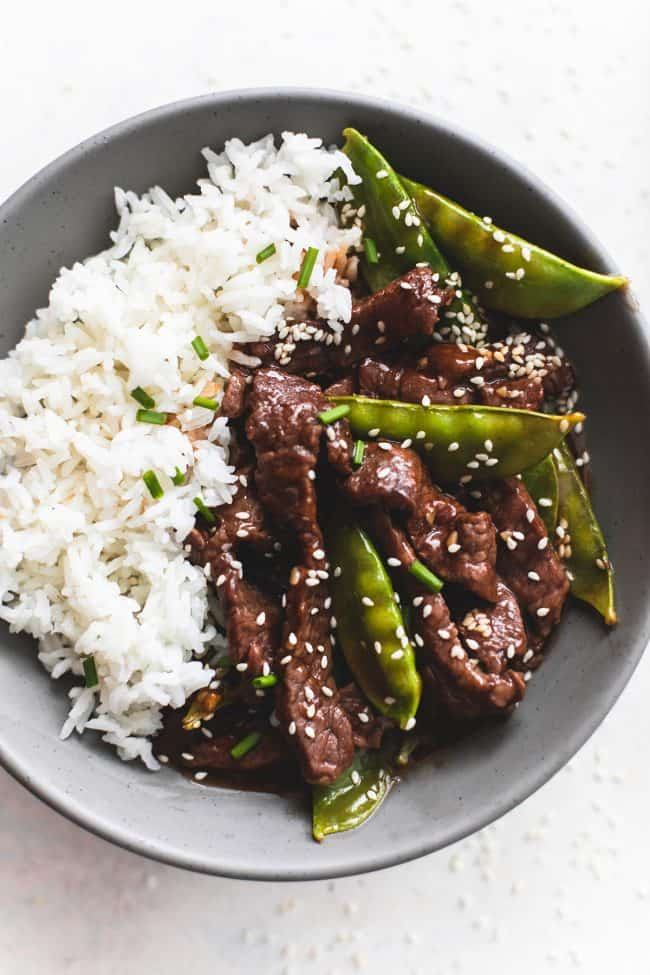 Honey sesame beef with rice on a black plate.
