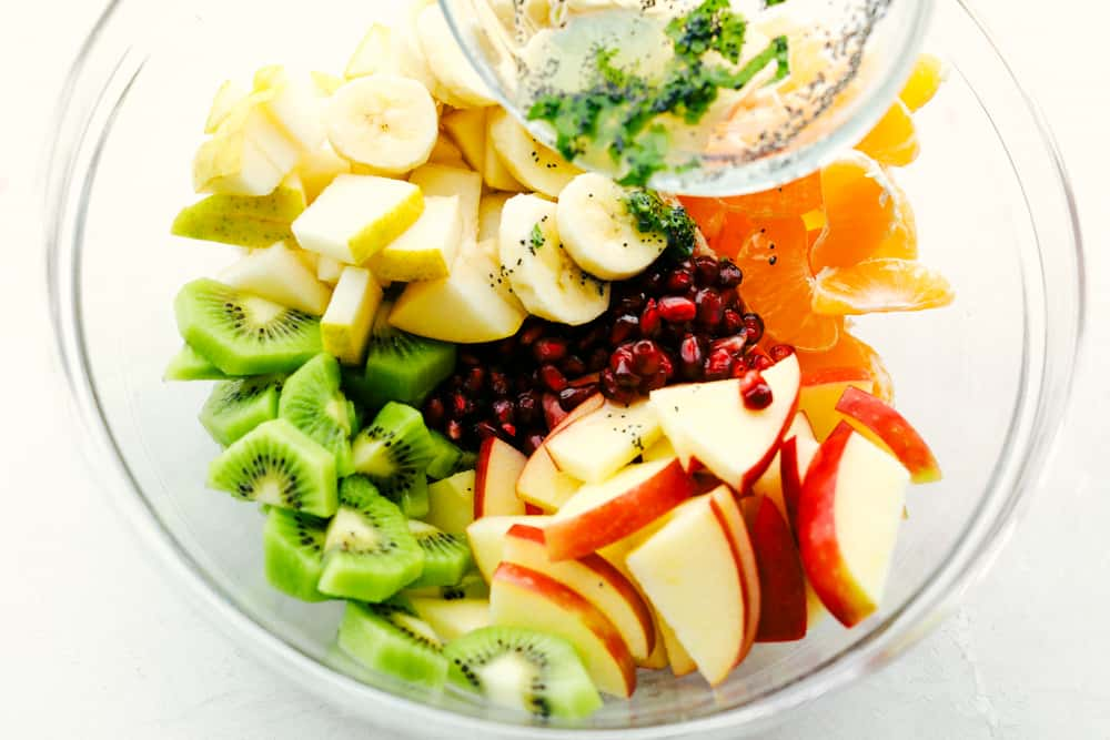 Winter Fruit Salad with bananas apples, oranges kiwi and pomegranates with poppyseed dressing.