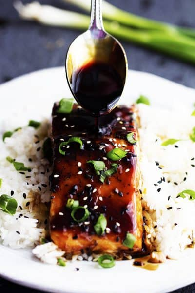 Baked Sesame Teriyaki Salmon on rice with a spoon pouring glaze on the salmon.