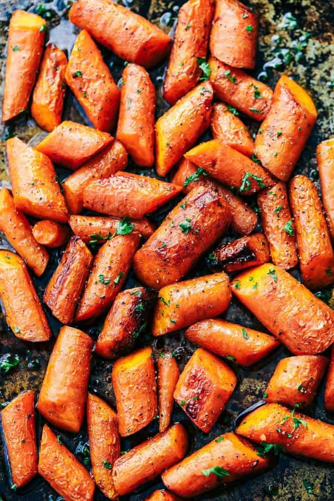 Roasted carrots spread out on a trayl